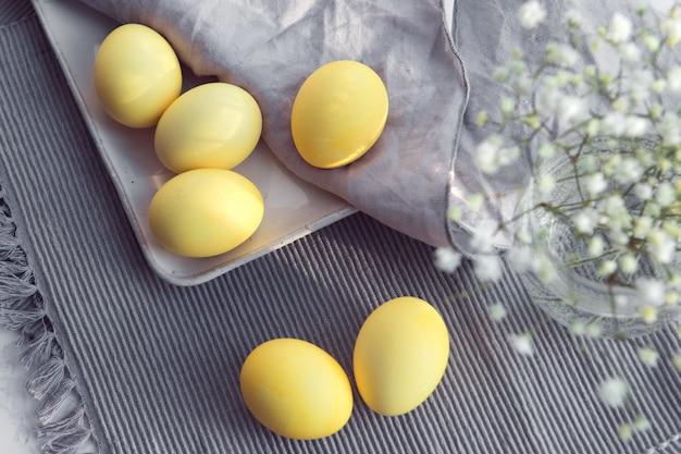 Ovos coloridos de amarelo na páscoa, flores de gipsófila decoradas em tecido cinza