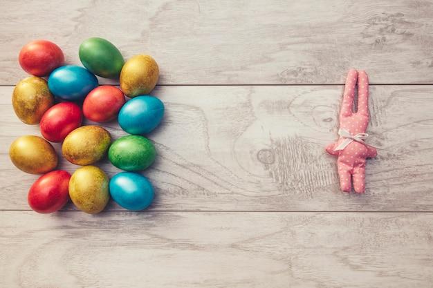 Ovos coloridos de férias de páscoa são brilhantes e coelho de brinquedo em uma mesa de madeira