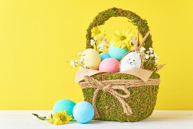Ovos coloridos de páscoa na cesta com decorações de flores sobre um fundo amarelo