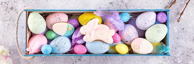 Ovos coloridos de páscoa pintaram em cores brilhantes com ninho de palha na caixa de madeira