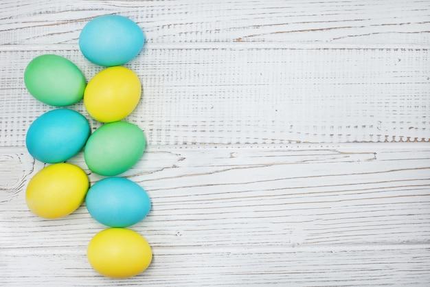 Ovos coloridos em um fundo branco de madeira. o conceito de páscoa e primavera.