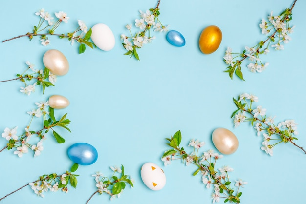 Ovos coloridos para a páscoa com ramos de cerejeira em flor sobre um fundo azul. postura plana, em branco para cartão postal, banner, espaço de cópia. vista do topo,