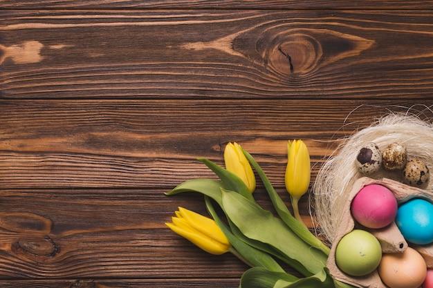Ovos coloridos perto de tulipas e ninhos