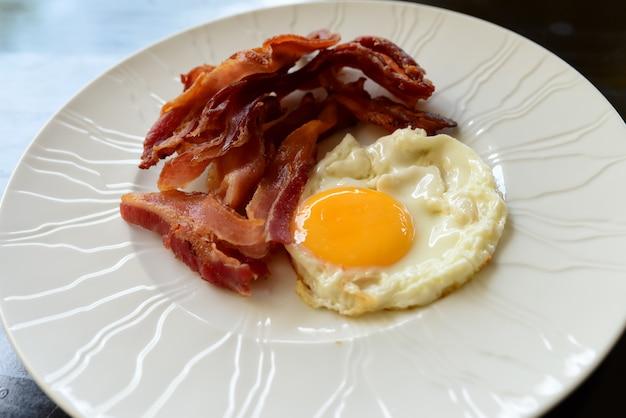Ovos com bacon no café da manhã na chapa branca