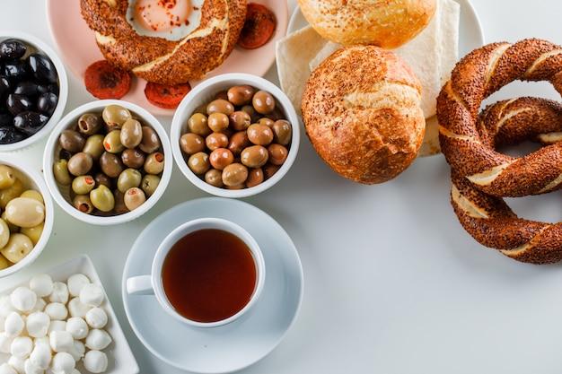 Ovos com linguiça em um prato com uma xícara de chá, pão turco, pão e azeitonas