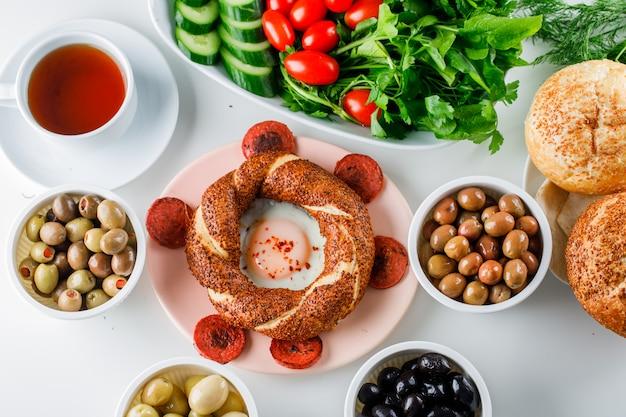 Ovos com linguiça em um prato com uma xícara de chá, pão turco, salada vista superior sobre uma superfície branca
