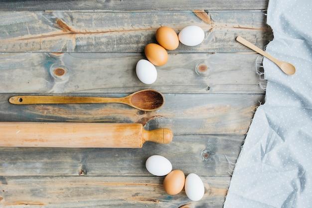 Ovos com rolo e colher em fundo de madeira