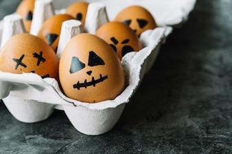 Ovos com rostos de Halloween retratados existentes na caixa