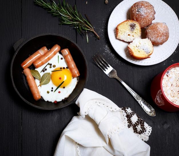 Ovos com salsichas em uma frigideira preta