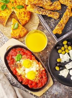 Ovos com tomate, queijo, azeitonas, suco de laranja e pão
