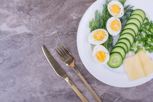 Ovos cozidos com ervas picadas e pepinos em um prato branco