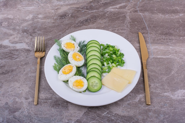 Ovos cozidos com pepinos fatiados e ervas em um prato branco.