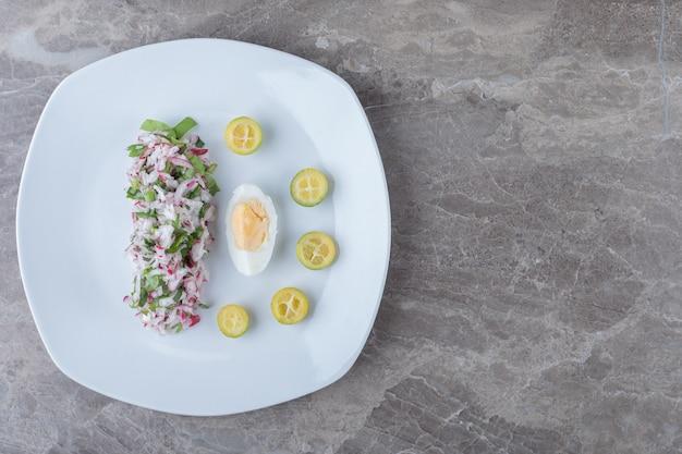 Ovos cozidos com salada como guarnição no prato branco.