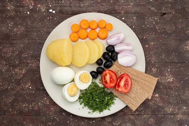 Ovos cozidos de vista superior com azeitonas verdes alho e tomate dentro da placa em marrom, café da manhã refeição vegetal comida