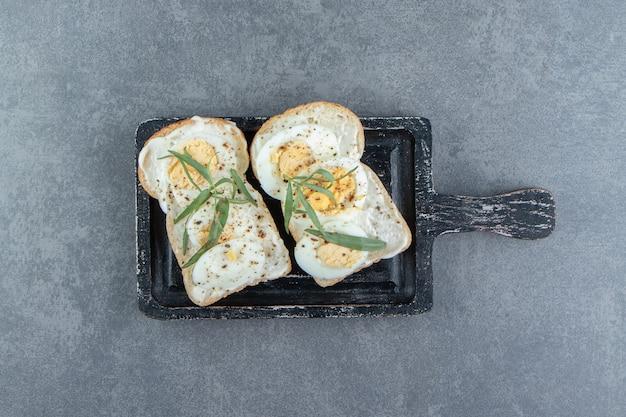 Ovos cozidos deliciosos no pão torrado.