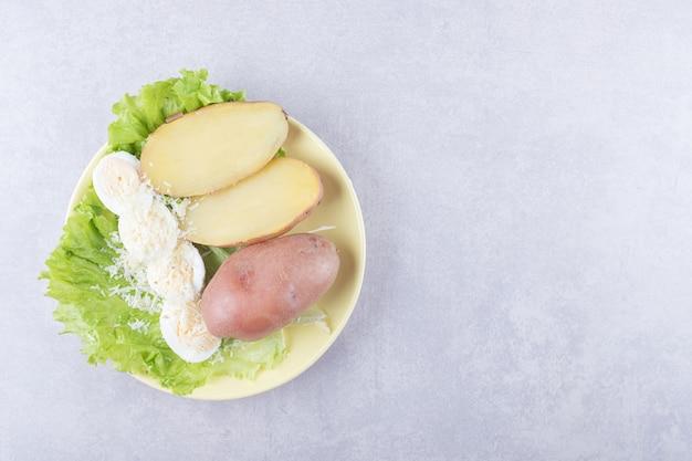 Ovos cozidos e batatas na placa amarela.