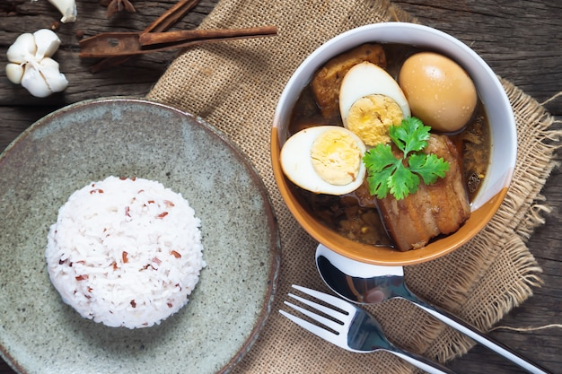 Ovos cozidos e carne de porco ou ovos e carne de porco em molho marrom em uma tigela com arroz na mesa de madeira