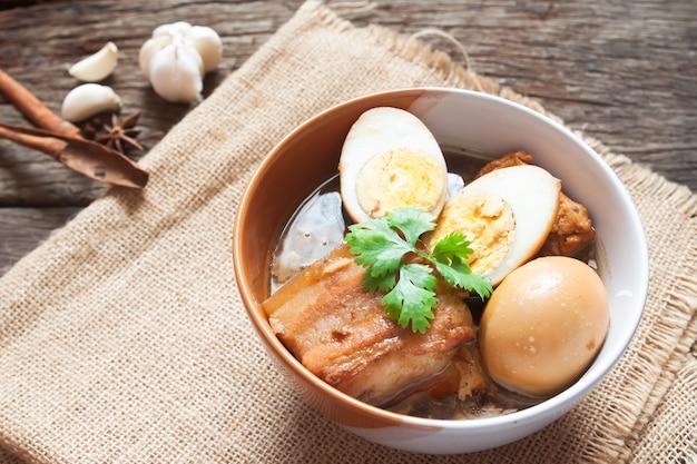 Ovos cozidos e carne de porco ou ovos e carne de porco em molho marrom em uma tigela com especiarias na mesa de madeira