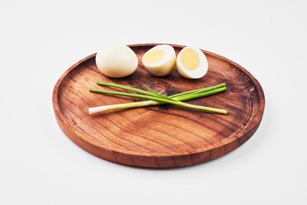 Ovos cozidos e cebolinha na travessa de madeira.