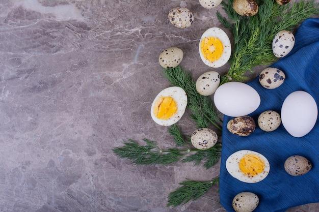 Ovos cozidos e crus na toalha azul.