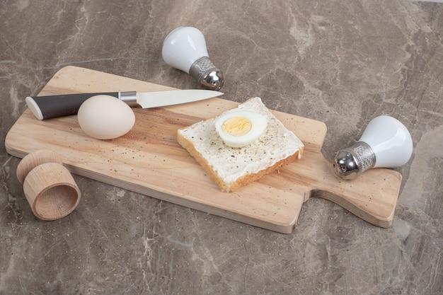 Ovos cozidos e fatia de torrada na tábua com faca e especiarias. foto de alta qualidade