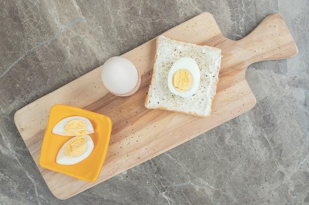 Ovos cozidos e fatias de torrada na tábua. foto de alta qualidade