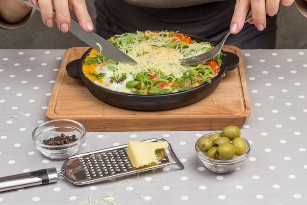 Ovos cozidos e legumes em uma panela. mãos segurando um garfo e uma faca.