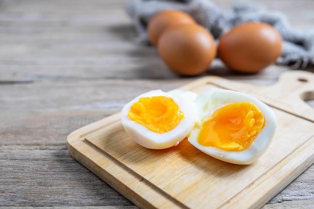 Ovos cozidos e ovos crus em uma mesa de madeira