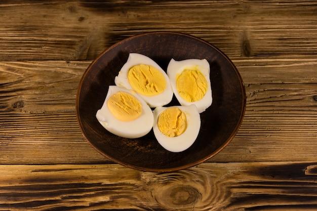 Ovos cozidos em um prato na mesa de madeira. vista do topo