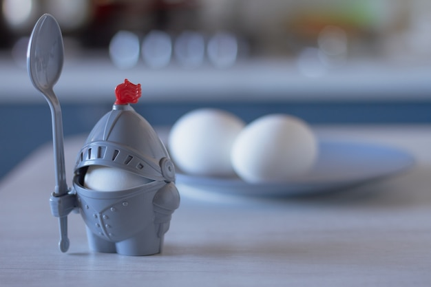 Ovos cozidos em uma sustentação sob a forma da armadura knightly da cor cinzenta em um fundo de madeira.