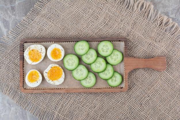 Ovos cozidos fatiados com pepino na placa de madeira. foto de alta qualidade