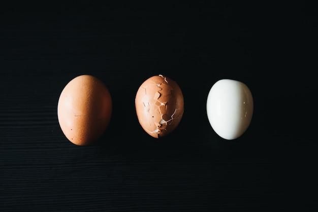 Ovos cozidos frescos frescos com casca ao lado no quadro negro de madeira (foco seletivo)