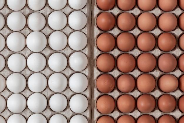 Ovos crus de frango vista superior de cor amarela e branca, deitado na caixa de papelão reciclável