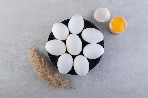 Ovos crus de galinha branca com gema e espigas de trigo colocadas na mesa de pedra.
