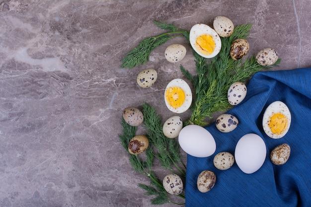 Ovos crus e cozidos com ervas em uma toalha azul