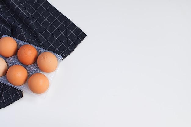 Ovos crus e guardanapo xadrez preto sobre fundo branco