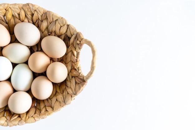 Ovos crus frescos da fazenda orgânica crua em uma cesta no branco