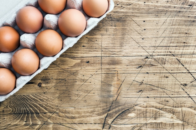 Ovos crus marrons em embalagens de fábrica em madeira rústico. copyspace