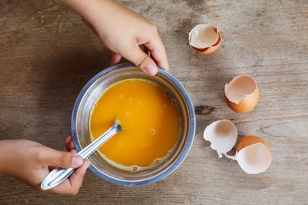 Ovos crus mexidos em uma tigela para cozinhar