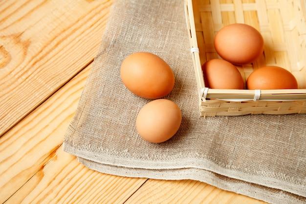Ovos crus na cesta de vime na mesa de madeira