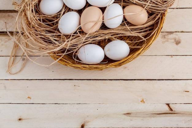 Ovos crus no feno em um assoalho de madeira
