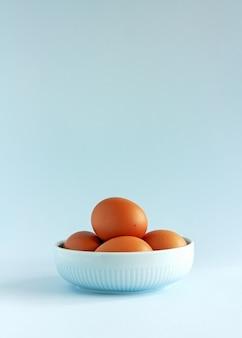 Ovos crus orgânicos frescos em uma tigela azul sobre azul