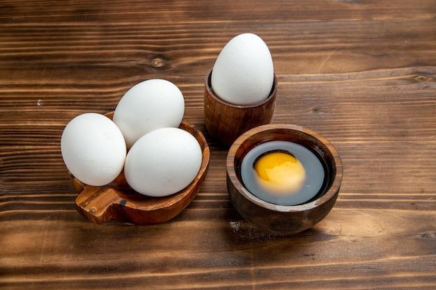 Ovos crus, produtos inteiros em uma superfície de madeira marrom, comida com ovos, café da manhã ovos mexidos