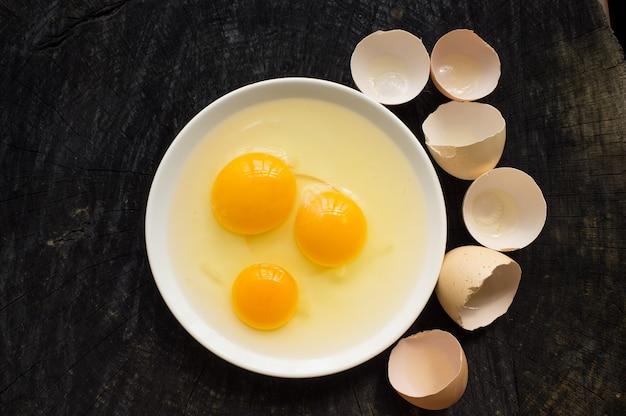 Ovos crus quebrados em uma chapa branca quebrada em uma mesa de madeira escura
