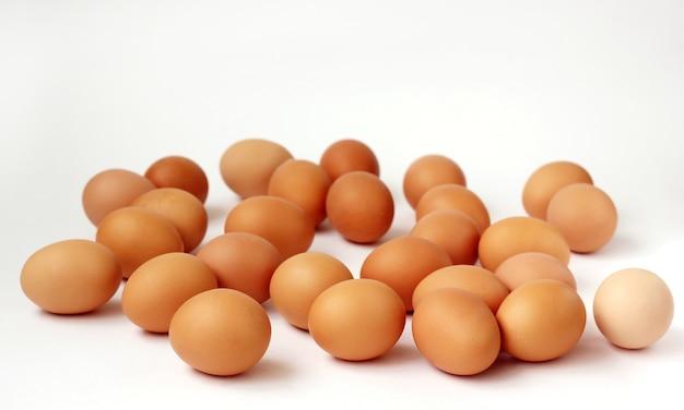 Ovos da galinha de brown que encontram-se em uma superfície branca.