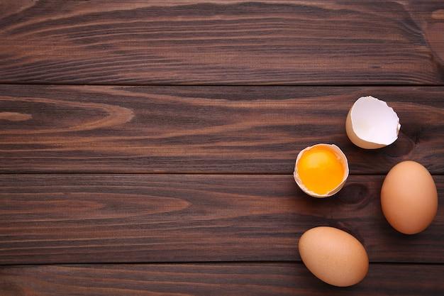 Ovos da galinha e metade com gema em um fundo marrom.
