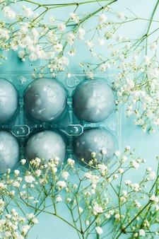 Ovos da páscoa azuis delicados entre as flores do gypsophila em um fundo azul.