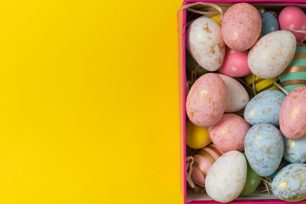 Ovos da páscoa coloridos do close up na caixa no fundo amarelo. vista superior do ovo festivo
