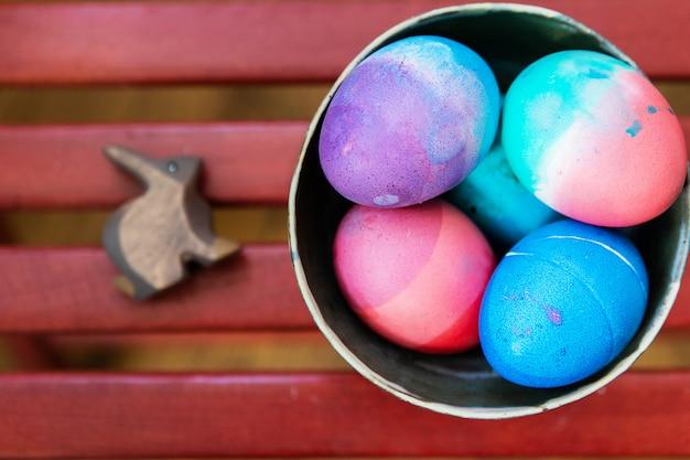 Ovos da páscoa coloridos em uma bacia cerâmica no fundo vermelho com o brinquedo de madeira do coelho. ovos brilhantes festivos coloridos pintados abstratamente em azul, rosa, verde e roxo.