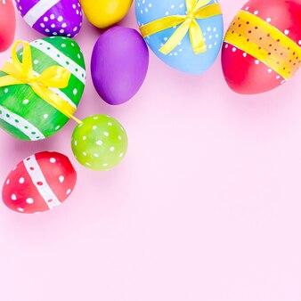 Ovos da páscoa coloridos na configuração pastel cor-de-rosa do plano do fundo. copie o espaço
